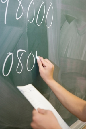 Student writing on blackboard